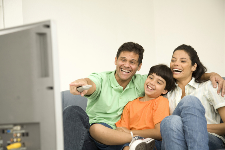 Boy with his parents sitting on a couch and watching television